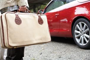 トランクを持った男性と赤い車の写真素材 [FYI03916590]
