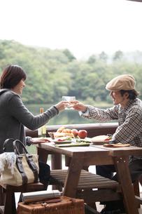 湖畔でテーブルを挟んで食事する男女の写真素材 [FYI03916632]