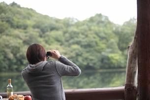 双眼鏡で湖を覗く女性の写真素材 [FYI03916635]