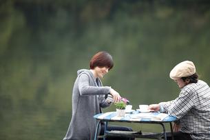 湖畔でテーブルを挟んで寛ぐ男女の写真素材 [FYI03916640]