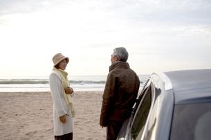 砂浜で語り合う男性と女性の写真素材 [FYI03916662]