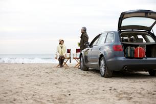 砂浜で語り合う男女とトランクの荷物の写真素材 [FYI03916675]