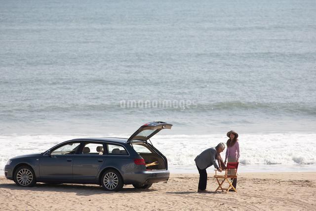 波打ち際の男女と車の写真素材 [FYI03916685]