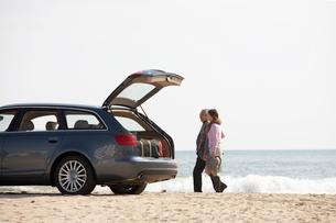 波打ち際を歩く男女と車の写真素材 [FYI03916687]