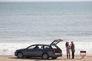 波打ち際の男女と車の写真素材 [FYI03916688]