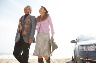 砂浜を歩く男女と車の写真素材 [FYI03916693]