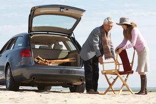 車のトランク前で椅子を組み立てる男女の写真素材 [FYI03916710]
