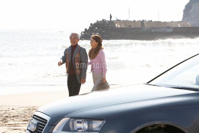 砂浜を歩く男女の写真素材 [FYI03916712]