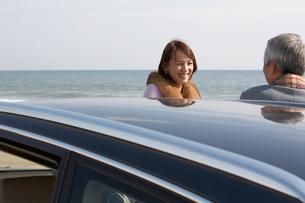 車のそばで語り合う男女の写真素材 [FYI03916713]