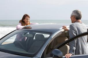 車をはさんで語り合う男女の写真素材 [FYI03916716]