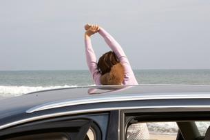 砂浜で体を伸ばす女性の写真素材 [FYI03916718]