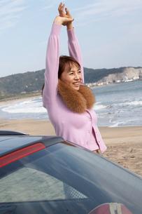 砂浜で体を伸ばす女性の写真素材 [FYI03916720]