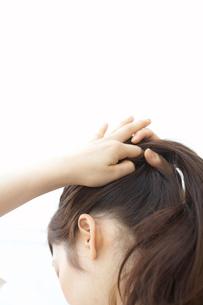 髪の毛を束ねる女性の写真素材 [FYI03916805]