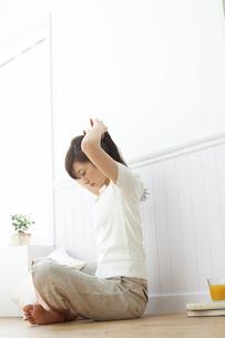 床に座り髪の毛を束ねる女性の写真素材 [FYI03916809]