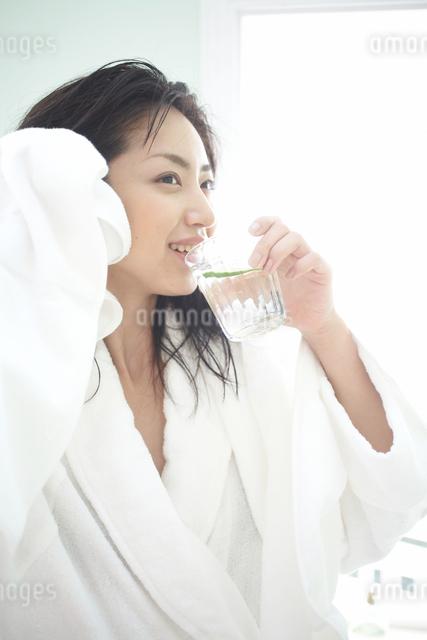 バスローブを着て水を飲む女性の写真素材 [FYI03916839]