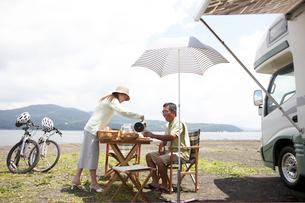 湖畔で食事を楽しむシニアカップルの写真素材 [FYI03916899]