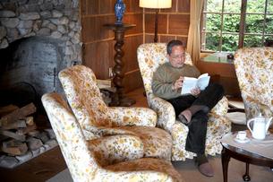ソファで本を読む男性の写真素材 [FYI03917057]