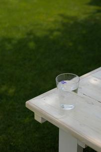 ウッドデッキの上の水の入ったコップの写真素材 [FYI03917339]