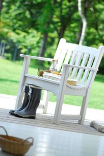 長靴と白いイスの上のじゃがいもとパプリカの写真素材 [FYI03917404]