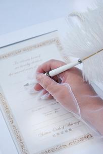 誓約書に署名をする新婦の手元の写真素材 [FYI03917605]