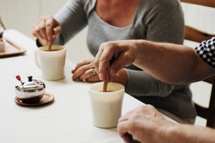 シナモンスティックでコーヒーをまぜる老夫婦の写真素材 [FYI03918264]