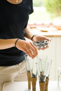 グラスにブルーベリーを入れる女性の手元の写真素材 [FYI03918381]