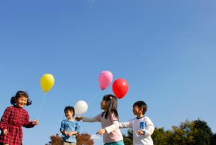 風船で遊ぶ子供4人(男女)の写真素材 [FYI03918886]