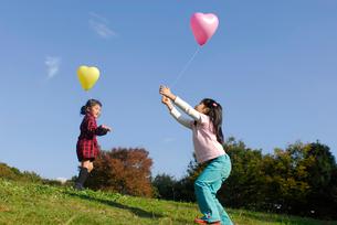 風船で遊ぶ女の子2人の写真素材 [FYI03918887]