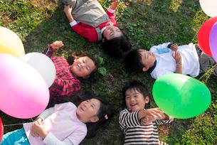 風船を持ち公園に寝転がる子供5人(男女)の写真素材 [FYI03918894]