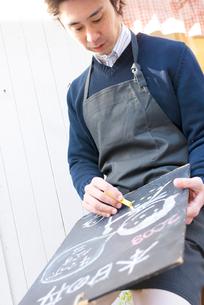 黒板に画を書く男性の写真素材 [FYI03918934]