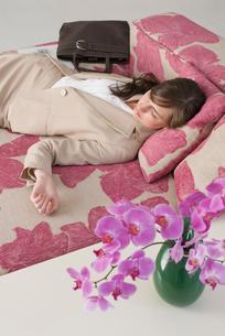 胡蝶蘭とソファで眠る女性の写真素材 [FYI03918987]