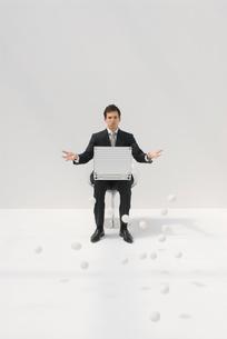 椅子に座るビジネスマンと白いボールの写真素材 [FYI03919000]