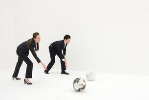 白と黒の地球儀を転がすビジネスマンと女性の写真素材 [FYI03919017]