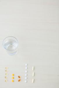 サプリメントと水の入ったグラスの写真素材 [FYI03919317]