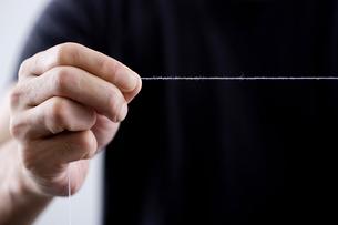 糸をひっばる男性の手元の写真素材 [FYI03919396]