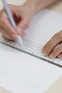 定規で紙に線を引く女性の手元の写真素材 [FYI03919410]
