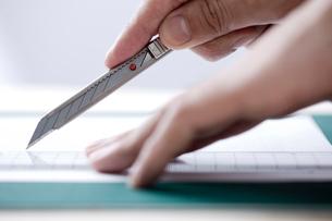 カッターで紙を切る男性の手元の写真素材 [FYI03919413]