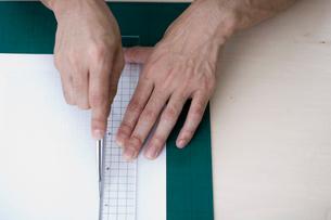 カッターで紙を切る男性の手元の写真素材 [FYI03919416]