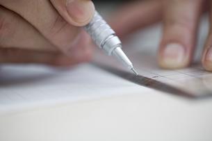 定規で紙に線を引く女性の手元の写真素材 [FYI03919421]