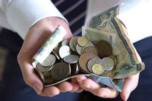 紙幣とコインを持つ男性の手元の写真素材 [FYI03919612]