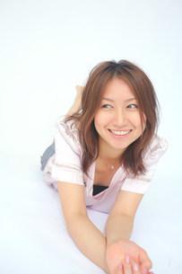 横になって笑っている女性の写真素材 [FYI03923555]