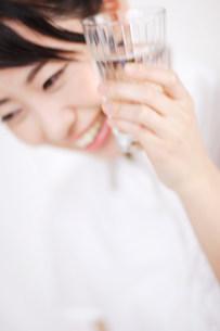 顔にコップを付けているいる女性の写真素材 [FYI03923588]