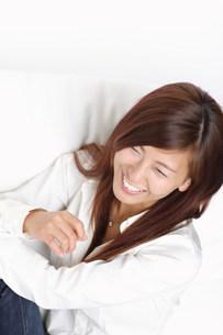 ソファーに座って笑っている女性の写真素材 [FYI03923589]
