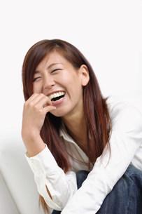 ソファーに座って笑っている女性の写真素材 [FYI03923590]