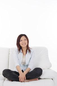 ソファーの上であぐらをかく女性の写真素材 [FYI03923616]