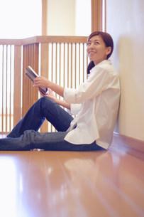 座って本を開いている女性の写真素材 [FYI03923632]