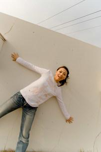 壁の前に立つ女性の写真素材 [FYI03923665]