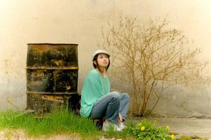 ドラム缶の前で座る女性の写真素材 [FYI03923678]