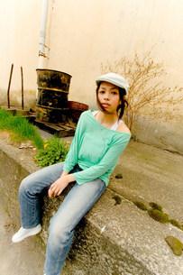 壁の前に座る女性の写真素材 [FYI03923680]