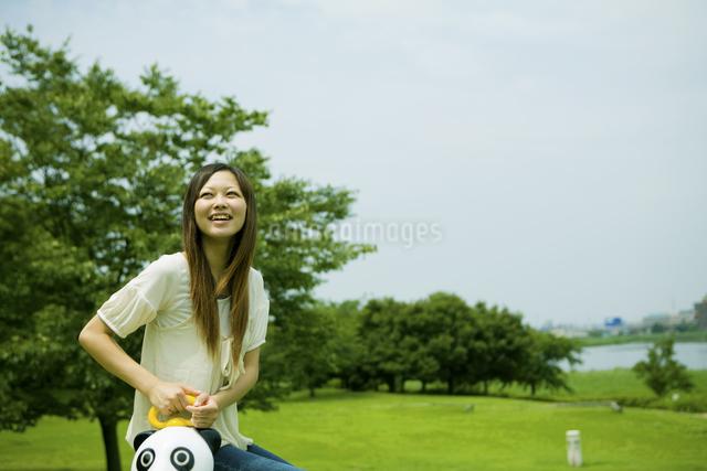 公園のパンダの遊具に腰掛ける20代女性の写真素材 [FYI03924025]